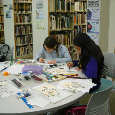 Students working on illustrations in library