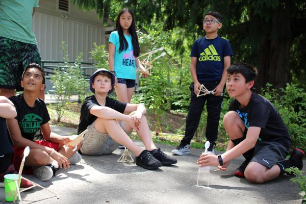 Students watch the marshmallow fly off the catapult