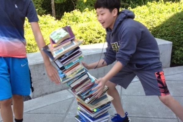 Students knocking over stack of books